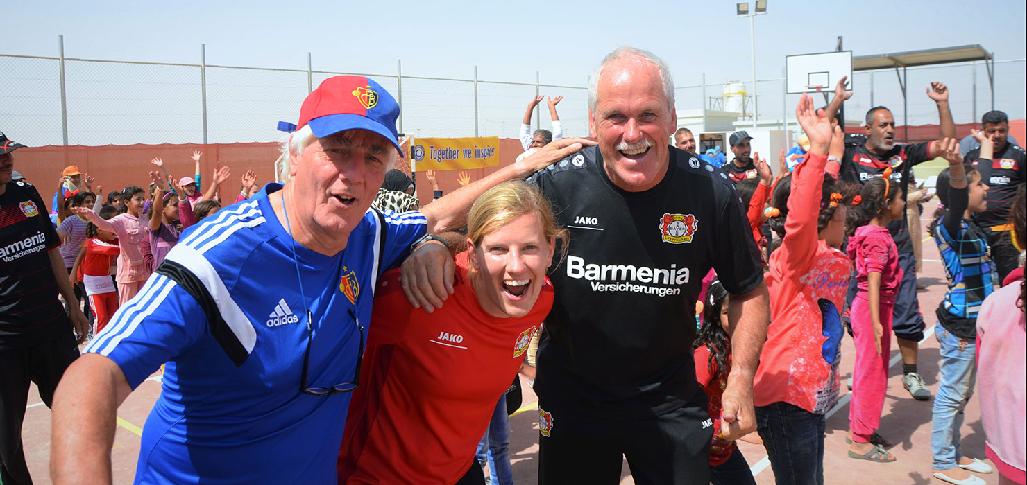 Three instructors, two men and a woman in the middle, are smiling at the camera