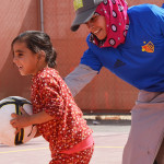 Female Young Coach instructing a girl holding a football