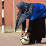 Female Young Coach holding a football