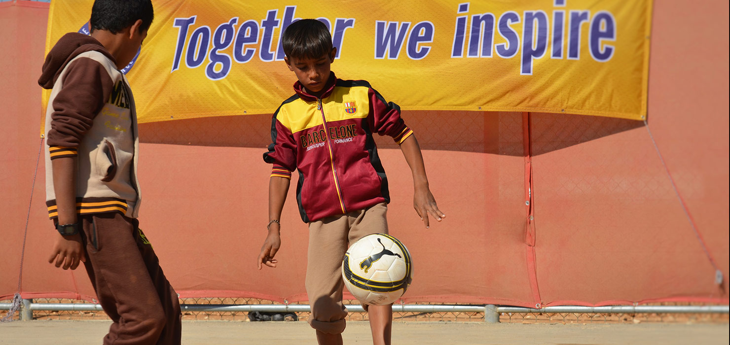 A boy is juggling a football with his foot