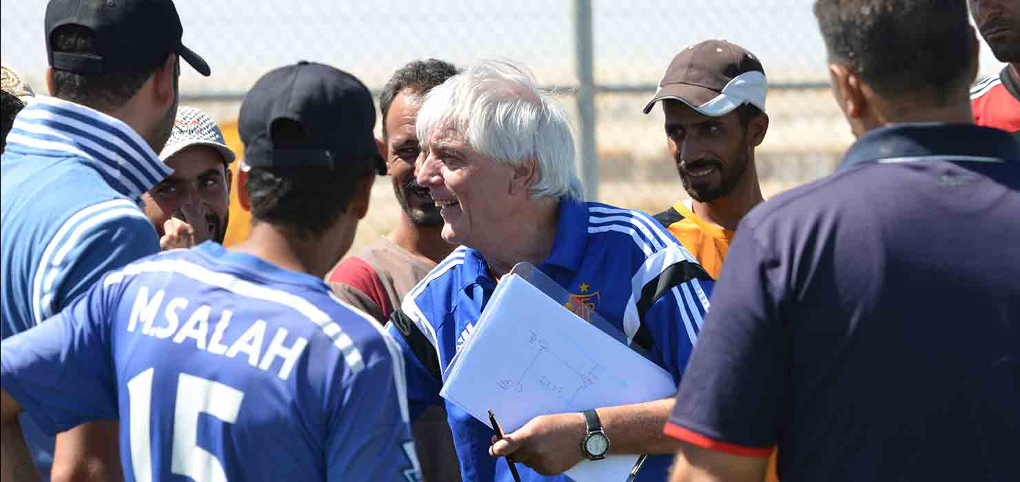 An instructor is holding a file and explaining football techniques to the Young coaches standing around him