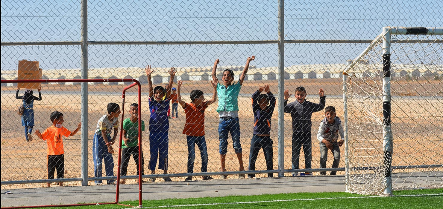 Children standing behind a fence in Azraq Refugee Camp